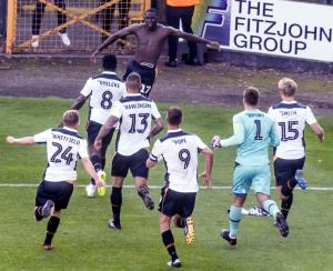 Idris Kanu celebrates his dramatic late goal against Exeter City with teammates.