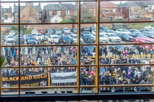 Protesters are framed in the main entrance window ahead of the Morecambe game.